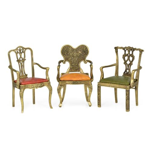 Set of miniature brass chairs with leather seats