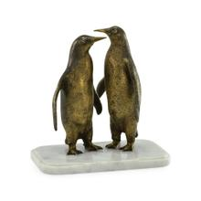 Two penguins on white marble base