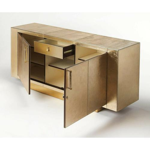 This modern buffet is magnificent in every conceivable way. Its sleek lines are adorned in finely tailored leather atop a brass platform base. Proving that all that glitters is not gold, its two doors with brass finished handle bar pulls open to reveal a