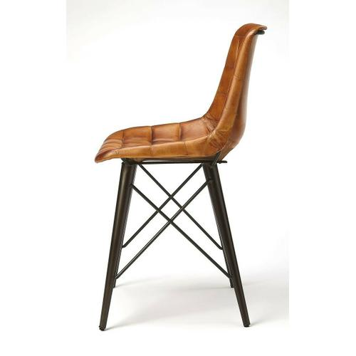 Mid-century modern with a symetrical leather pattern; this go-everywhere molded chair form gets an upgrade with the compliment of Warm Brown quilted leather and black metal frame. The soft taper metal legs bring a bit of retro modern to the overall style. Set this chair at a table or in a corner; it will not go unnoticed.