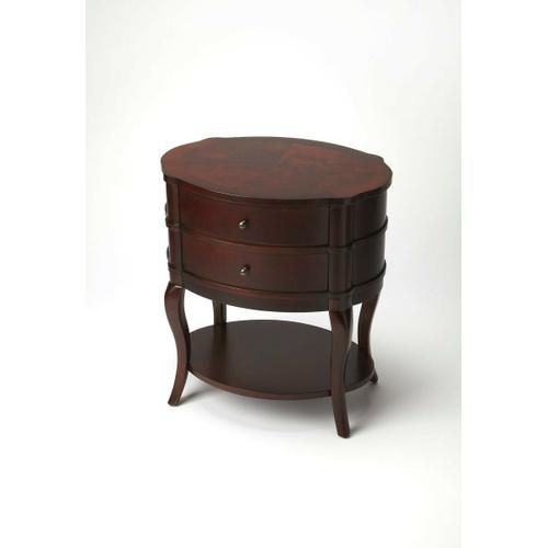 With polished curves and subtle finesse, this transitionally styled table has a sleek,functional design that suits almost every decor. Featuring a Plantation Cherry finish and two drawers with antique brass-finished hardware plus a bottom shelf, this cla