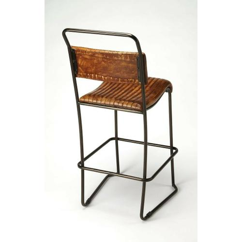Pairing a black-finished metal base with a ribbed leather seat, this bar stool brings a bit of sturdy and rustic industrial style to your space, with its curvaceous seat and supple leather it is sure to delight. Cluster several at your kitchen island to g