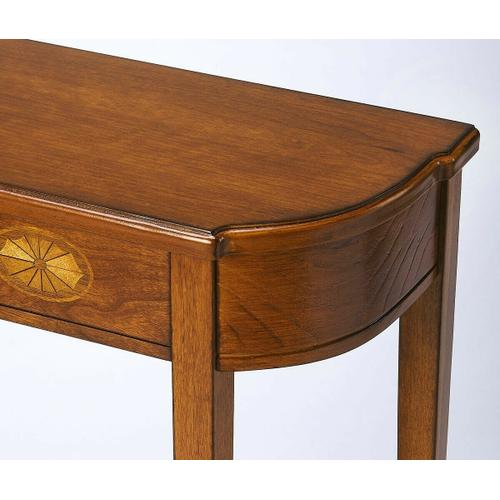 Butler Specialty Company - A spot of elegance for a small space, this Console table's harmonious design begins with the slender legs, gracefully tapered. The beautiful symmetry of tabletop and bottom shelf adds to the effect, which is consummated in the linen-fold inlay on the front and the gleaming Olive Ash Burl finish on the cherry veneer.