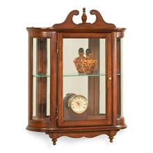 This distinctive wall curio is both functional and beautiful with two adjustable glass shelves and a mirrored back to display your prized possessions. The curved glass sides make it very unique. The glass paneled door features antique brass finished hardware. This future heirloom is made of select solid woods and wood veneers.