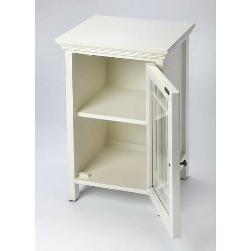 Packing fashion as well as function, this stylish Chairside Table features a nine-panel glass door; contemporary fretwork, white finish, a gleaming brass-finished door pull that opens to a convenient storage space with a shelf. Crafted in Mango wood soli