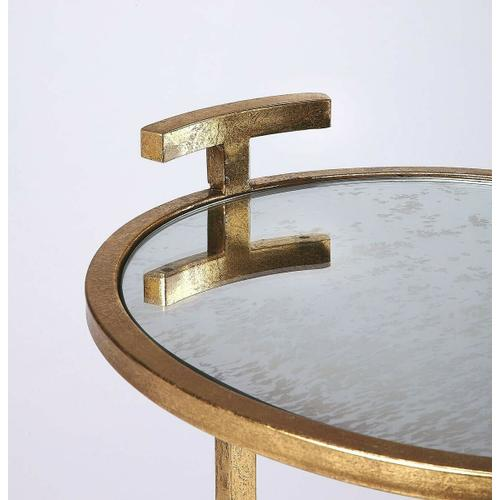 Clean, contemporary, and your sofa or chair's new sidekick, this side table lends a helping hand for a lamp, your favorite beverage, and more. Its ovular, minimalist design features a stylish gold finished iron frame with an antique mirrored mirrored glas