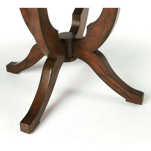 This foyer table is a captivating addition not only in the foyer, but in other living or office spaces. Crafted from mahogany wood solids on a four-legged base, its arms support the table's round mahogany veneer top in uplifting fashion in a rich, dark Co