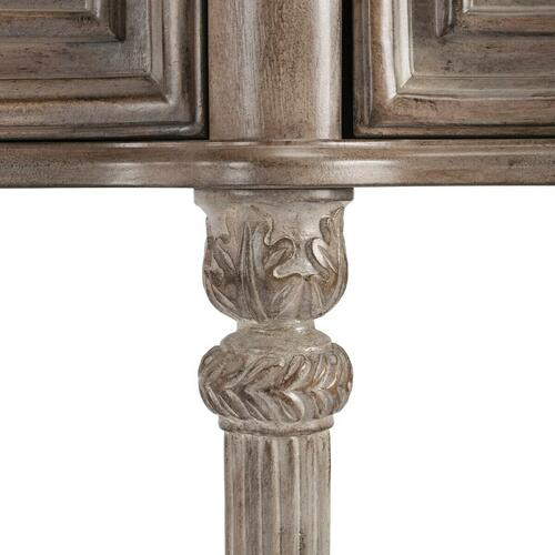 This gorgeous console exudes grandeur. Crafted from select solid woods, wood products and choice veneers, it features a shapely top, lower shelf and drawer fronts all done in oak veneers. The legs have a fluted design with hand carved acanthus leaf detail